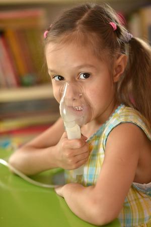 tonsillitis: Portrait of a lovely little girl with inhaler