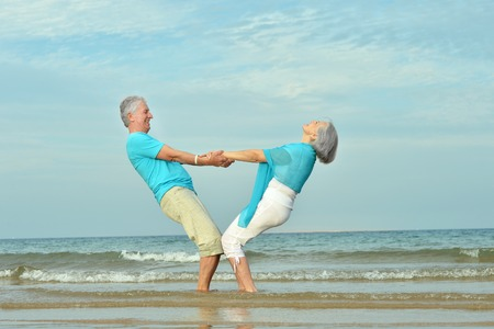 persona de la tercera edad: Hermosa feliz pareja de ancianos caminando por la orilla del mar