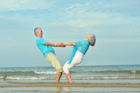 Mooie gelukkige paar ouderen lopen langs de kust Stockfoto