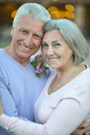 Happy beautiful elderly couple standing embracing outdoors photo
