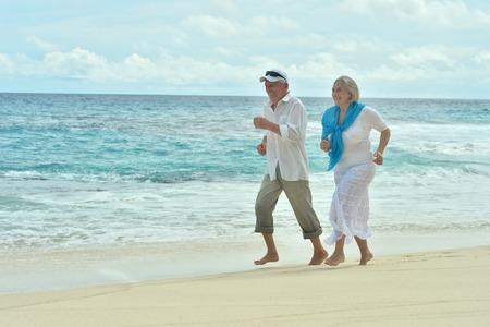 Portrait of a happy elderly couple running  on beach