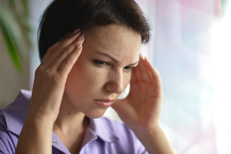 contagious: Sick woman with headache at home with pills