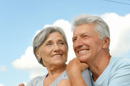 Gelukkig bejaarde echtpaar poseren tegen de hemel Stockfoto