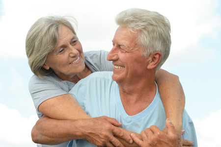 man woman hugging: Elderly couple relaxing on a sunny day together Stock Photo