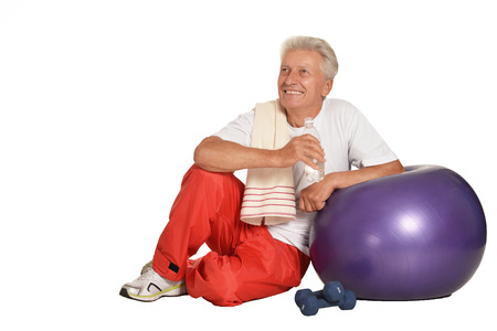 old man happy: Portrait Of A Senior Man sitting on a floor with water after exercising isolated on white Stock Photo