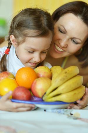 eating fruits: Madre e hija comer frutas en la mesa en casa
