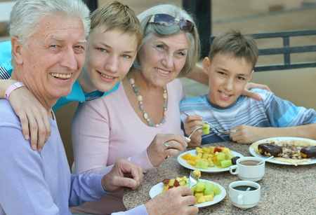 abuelos: Abuelos con nietos en el desayuno en el resort tropical Foto de archivo