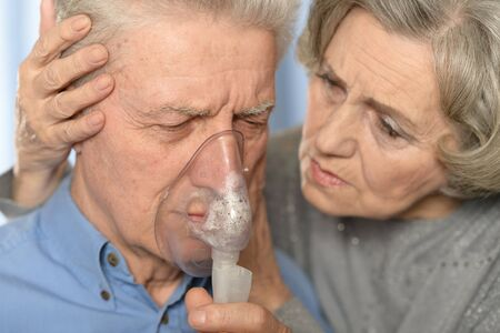 Portrait of ill senior couple, man with inhaler