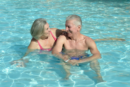 natural pool: Senior couple relaxing at pool at hotel resort Stock Photo