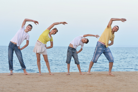 mam: Portrait of a happy family at beach in summer doing exercises