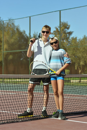 sibling rivalry: Portrait of two brothers playing at tennis court