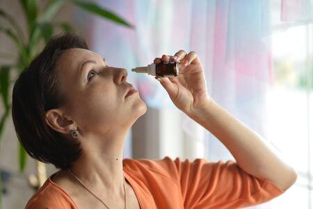 nasal drops: Portrait of sick Woman with nasal drops Stock Photo