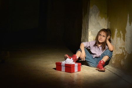 abused: Lonely little girl   in a dark cellar with gift box