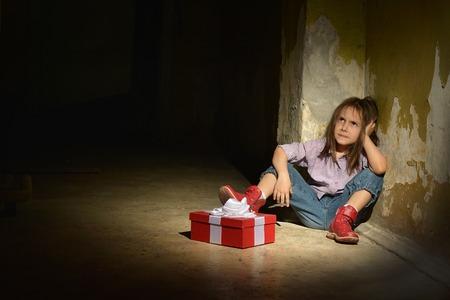 mujeres tristes: Niña sola en un sótano oscuro con caja de regalo
