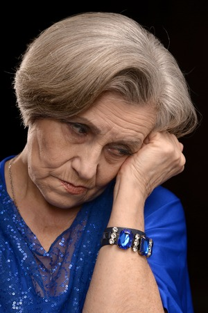 lamentable: portrait of thoughtful elderly woman in white on a black background