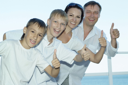 mam: Happy family of four showing thumbs up at sea Stock Photo