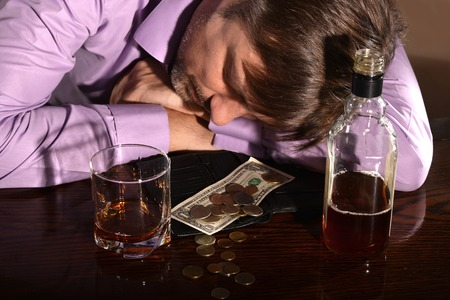 boozer: Young man sleeping with whiskey and money at table