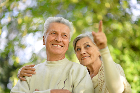 old sign: Happy senior couple relax in autumn park,woman pointing at something