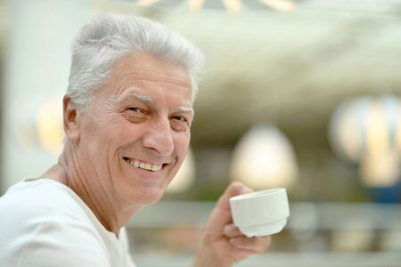 hombre tomando cafe: Viejo caf� lindo hombre bebiendo en la mesa