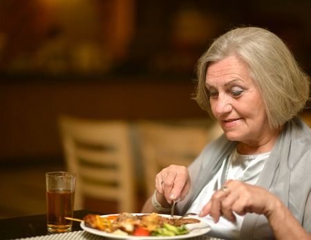 dinner: Senior woman having a dinner at restaurant