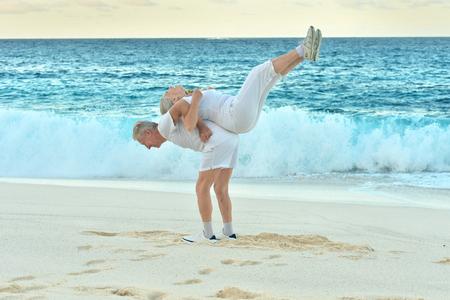 Felice coppia senior esercizio in estate sulla riva del mare