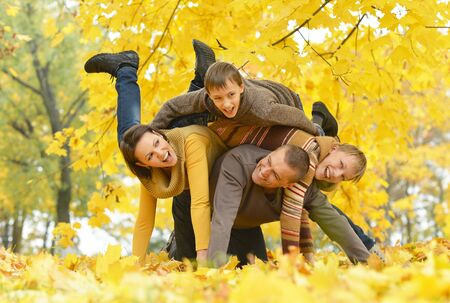 Portrait of happy family playing in autumn park