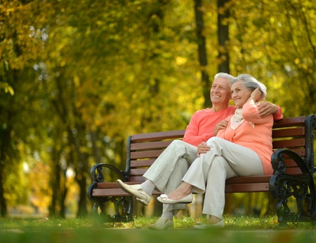 Happy elderly couple sitting on bench in autumn park Foto de archivo