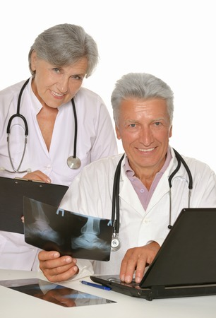 white coats: Doctors in white coats with stethoscopes looking at x-ray Stock Photo