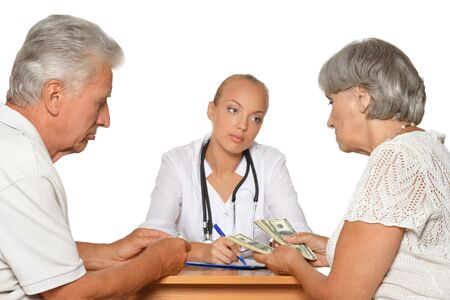 giving money: Old Woman giving money to female doctor on white Stock Photo