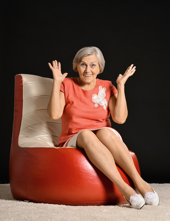 mujer sentada: Anciana sentada en sillón rojo en estudio oscuro