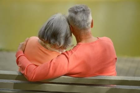grandparents: Happy elderly couple sitting on bench in autumn park Stock Photo