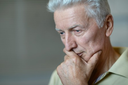 male senior adults: close-up portrait of a senior man thinking about something Stock Photo