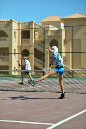 sibling rivalry: Two cute brothers playing at tennis court Stock Photo