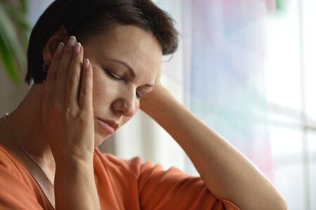 dolor de cabeza: Retrato de una mujer enferma con dolor de cabeza en casa
