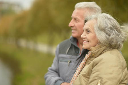 mature people: Elderly couple smilling together over natural background Stock Photo