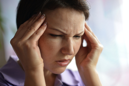 tonsillitis: Sick woman with headache at home with pills