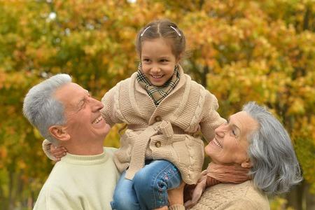 abuelo: Abuelos con su nieta en el parque del otoño Foto de archivo
