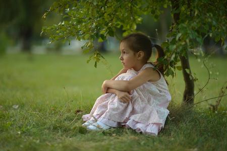 mignonne petite fille: Petite fille assise sous un arbre sur la nature