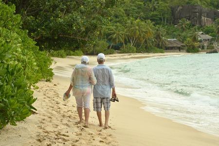 indian couple: Beautiful happy elderly couple walking along the seashore Stock Photo