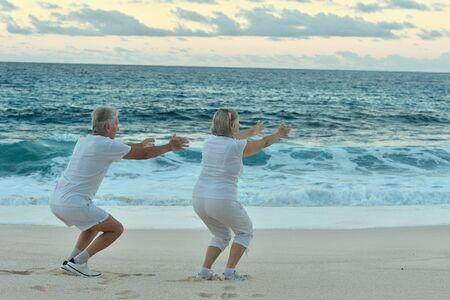 senior exercising: Happy Senior couple exercising in summer on  seashore Stock Photo