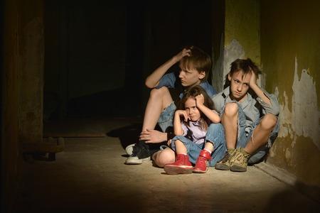 mujer golpeada: Los niños pequeños y una niña en un sótano oscuro