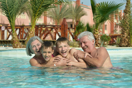 grandparents: Happy grandparents with their grandchildren in pool on vacation