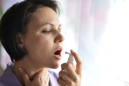 spay: Portrait of a sick Woman squirting throat