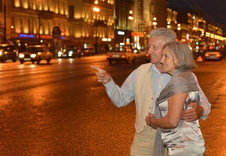 copule: Portrait of amusing old couple on night street