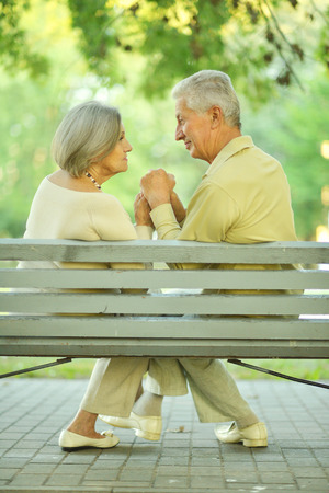 copule: Portrait of amusing old couple sitting on bench
