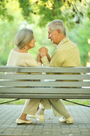copule: Retrato de divertida pareja de ancianos sentados en el banco Foto de archivo
