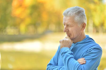 hombre pensando: Retrato del hombre mayor que piensa en algo al aire libre