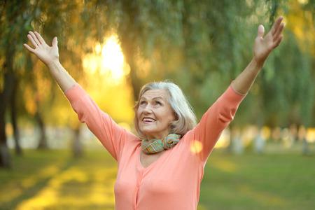 Senior vrouw wandelen in het park in de herfst Stockfoto