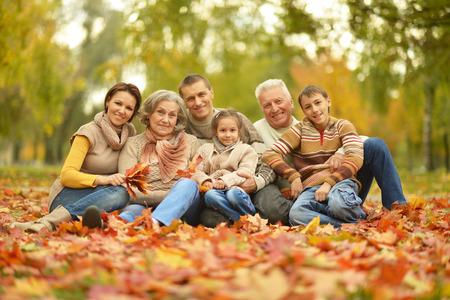 familias jovenes: Retrato de familia feliz de relax en el bosque de otoño Foto de archivo