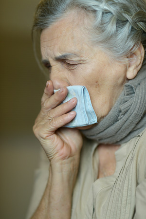 fells: Mature woman fells ill a cold at home Stock Photo